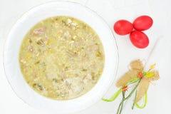 Conceito com sopa da Páscoa, os ovos vermelhos e a vela da Páscoa Fotografia de Stock Royalty Free