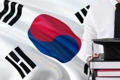 Conceito coreano sul bem sucedido da educação do estudante Guardando livros e tampão da graduação sobre o fundo da bandeira de Co imagem de stock