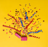 Conceito criativo com a decoração festiva no amarelo Corações dos confetes e estrelas, fitas, caixa de presente Fotografia de Stock