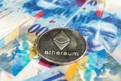 Conceito cripto da moeda - um Ethereum com moeda do franco suíço, Suíça foto de stock