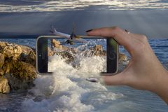 conceito 3D com por do sol móvel dos aviões do mar da mão fotos de stock royalty free
