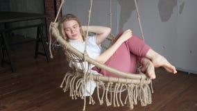 Conceito da alegria, menina loura nova bonita que relaxa e que gerencie ao redor no balanço na sala acolhedor do sótão video estoque