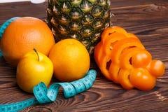 Conceito da aptidão com abacaxi, laranjas, maçãs, pimenta doce e a fita de medição foto de stock royalty free
