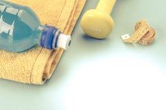 Conceito da aptidão com pesos, toalha, medida da fita e a garrafa/peso amarelo, toalha, medida da fita e garrafa toned Copie o es imagem de stock