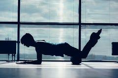 Conceito da aptidão, do esporte, do treinamento e do estilo de vida - mulher que faz pilates no assoalho com contorno do rolo da  foto de stock