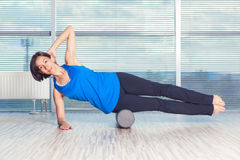 Conceito da aptidão, do esporte, do treinamento e do estilo de vida - mulher que faz pilates no assoalho com rolo da espuma fotos de stock