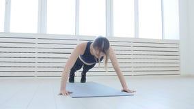 Conceito da aptidão do esporte e da casa Jovem mulher que faz exercícios da aptidão em um interior branco vídeos de arquivo