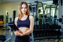 Conceito da aptidão, do exercício, do gym, da tecnologia e do estilo de vida - jovem mulher que guarda uma prancheta com um plano Imagens de Stock