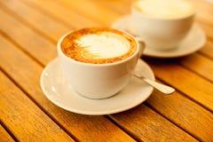 Conceito da arte do Latte Dois copos com cappuccino Foto de Stock Royalty Free