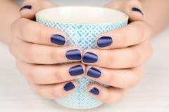 Conceito da arte do prego Mãos fêmeas bonitas com o tratamento de mãos puro que guarda o copo fotografia de stock royalty free