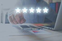 Conceito da avaliação Homem de negócios que aponta a estrela cinco à avaliação do aumento da empresa Fotos de Stock Royalty Free
