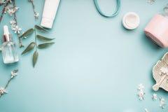 Conceito da beleza com os produtos, as folhas do verde e a flor de cerejeira cosméticos faciais no desktop azul pastel fotografia de stock