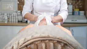 Conceito da beleza Feche acima da cara fêmea nova que está sendo wraped pela toalha para aquecer a pele facial antes do procedime filme