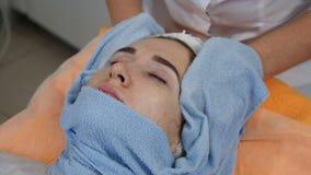 Conceito da beleza Feche acima da cara fêmea que está sendo wraped pela toalha para aquecer a pele facial antes do procedimento f filme