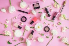 Conceito da beleza Mesa feminino com cosméticos da mulher e as flores brancas no fundo cor-de-rosa Configuração lisa, vista super Fotos de Stock Royalty Free