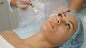 Conceito da beleza O esteticista prepara uma cara do ` s do cliente para mesotherapy limpando o com uma almofada de algodão Dispa filme