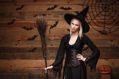 Conceito da bruxa de Dia das Bruxas - bruxa 'sexy' feliz de Dia das Bruxas que guarda o levantamento com furar a expressão facial fotografia de stock