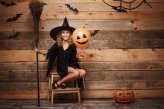 Conceito da bruxa de Dia das Bruxas - tiro completo da criança caucasiano pequena da bruxa que levanta com o cabo de vassoura mág fotografia de stock