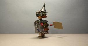 Conceito da busca de trabalho O robô quer obter um trabalho Robô desempregado engraçado do brinquedo que anda com um sinal do car vídeos de arquivo