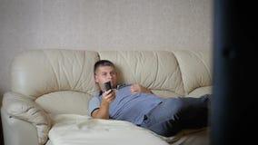 Conceito da casa, dos povos, da tecnologia e do entretenimento, homem com a tevê de observação de controle remoto em casa vídeos de arquivo