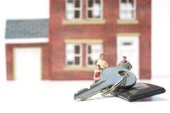 Conceito da casa familiar com casa e os povos modelo no backgro branco imagens de stock royalty free