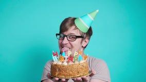 Conceito da celebra??o e do divertimento Homem novo louco feliz de sorriso no chapéu do partido que guarda um bolo de aniversário vídeos de arquivo