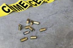Conceito da cena do crime com uma arma, uma fita da cena do crime e umas embalagens da bala Imagem de Stock Royalty Free
