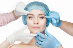 Conceito da cirurgia plástica Mãos do doutor nas luvas que tocam na cara da mulher fotos de stock