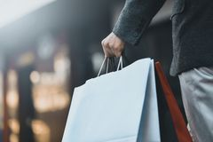 Conceito da compra do homem e dos sacos guardar, imagens do close up Feche acima dos sacos de compras de papel na mão masculina imagens de stock royalty free