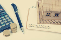 Conceito da compra e do seguro do alojamento Tabela da mesa de escritório com opinião superior das fontes Calculadora moedas dour fotos de stock royalty free
