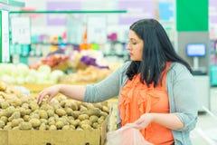 Conceito da compra Mulher que escolhe e que toma batatas na loja do supermercado Fotografia de Stock Royalty Free