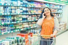 Conceito da compra Telefone da mulher e carrinho de compras faladores guardar na loja do supermercado perto das janelas da compra foto de stock royalty free