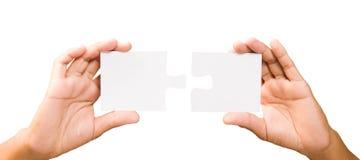 Conceito da conexão mãos com partes de enigma no backgro branco Imagem de Stock