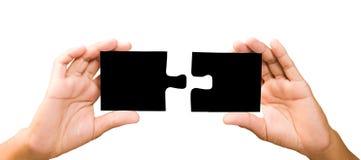 Conceito da conexão mãos com partes de enigma preto Imagens de Stock