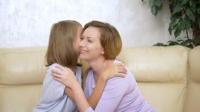 Conceito da confiança da família, filha feliz que sussurra um segredo a sua mãe que senta-se no sofá na sala de visitas video estoque