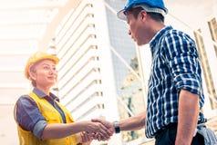 Conceito da construção e do coordenador Trabalhador da construção no encontro de agitação das mãos do uniforme protetor imagem de stock