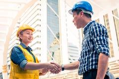 Conceito da construção e do coordenador Trabalhador da construção no uniforme protetor que agita as mãos que encontram-se para o  fotografia de stock royalty free