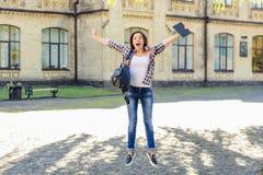 Conceito da construção da faculdade da educação do luch da realização do exame bom Estudante fêmea de salto entusiasmado feliz qu foto de stock royalty free