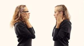 Conceito da conversa do auto Jovem mulher que fala a si mesma, mostrando gestos Retrato dobro de duas vistas laterais diferentes Imagens de Stock Royalty Free