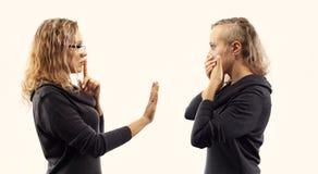 Conceito da conversa do auto Jovem mulher que fala a si mesma, mostrando gestos Retrato dobro de duas vistas laterais diferentes Foto de Stock Royalty Free