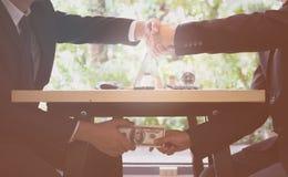 Conceito da corrupção feche acima do homem de negócios dois que agita as mãos e que recebe o dinheiro dos dólares Dinheiro do sub imagem de stock