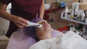 Conceito da cosmetologia e da tecnologia - esteticista com o dispositivo do microdermabrasion que faz a esfoliação da cara à jove vídeos de arquivo