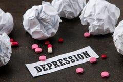 Conceito da depressão Doença psicológica a depressão da inscrição e as bolas de papel amarrotadas em um fundo escuro imagens de stock royalty free
