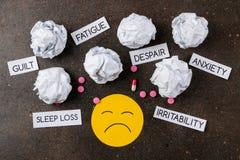 Conceito da depressão Doença psicológica smiley e sintomas tristes da depressão e dos comprimidos em um fundo escuro Vista de aci foto de stock