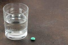 Conceito da depressão Doença psicológica um vidro com água e uma tabuleta em um fundo escuro Lugar para o texto imagem de stock royalty free