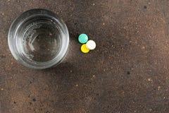 Conceito da depressão Doença psicológica um vidro com água e uma tabuleta em um fundo escuro Lugar para o texto Vista superior fotos de stock