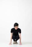 Conceito da determinação Mulher ocasional na roupa preta em posição running do começo que olha a câmera foto de stock