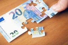 Conceito da economia: entregue a colocação de uma parte sobre um enigma do euro 20 Fotografia de Stock Royalty Free