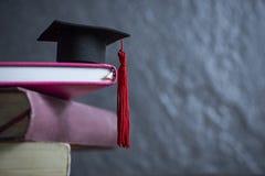 Conceito da educação com tampão da graduação em um livro com fundo escuro foto de stock royalty free