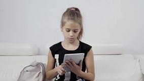 Conceito da educação, da escola, da tecnologia e do Internet - menina pequena do estudante com o PC da tabuleta na escola ou na c vídeos de arquivo